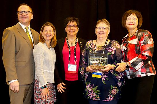 This year's recipient, Margaret Tardif (second from right), is handed the Award by Darren Hill and Chris Fonseca of FCM's Women Committee, then-President Jenny Gerbasi, and Ann MacLean.