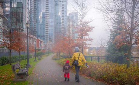 Woman and child holding hands walking in downtown Vancouver