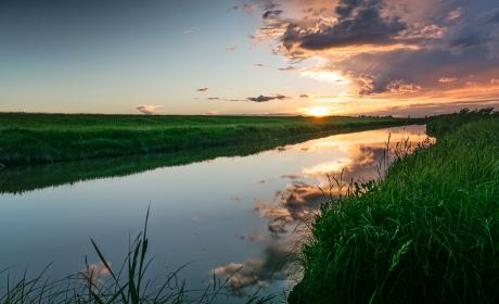 Sunset reflected on Seien River, flocked by long grass in Manitoba
