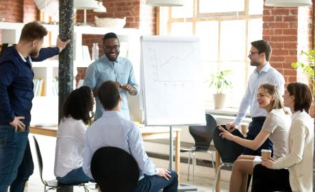 Excited coach makes flipchart presentation for employees