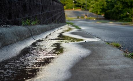 A paved road lined with a dark retained wall slopes downhill, water from a recent rainfall gathers along the gutter
