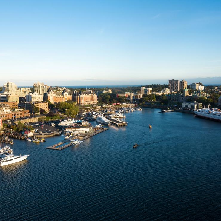 The sunbathed harbour in Victoria, BC sits between the mountains and the ocean.